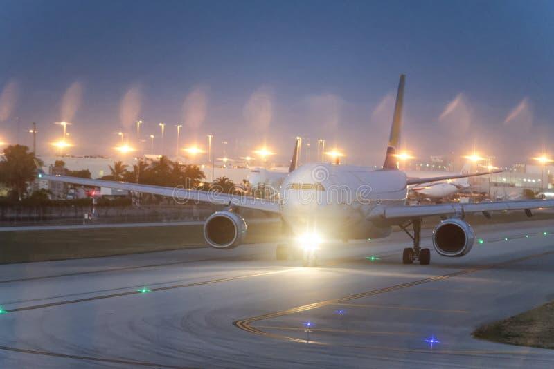 Opinião da noite do avião na pista de decolagem aproximadamente a decolar foto de stock royalty free