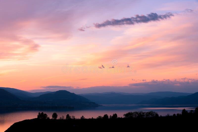 Opinião da noite do céu do por do sol sobre o lago com as silhuetas das montanhas e das árvores fotos de stock