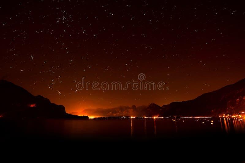 Opinião da noite do lago com as luzes no horizonte e no céu estrelado imagens de stock royalty free