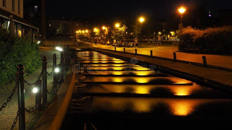 Opinião da noite do rio que flui abaixo das escadas na ilha do moinho em Bydgoszcz, Polônia imagem de stock