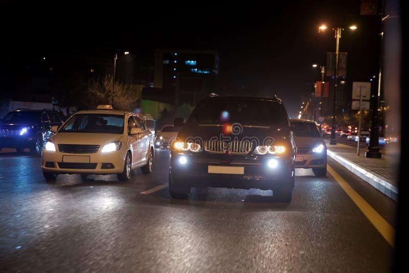Opinião da noite dos carros Estrada na cidade na noite com luz elétrica amarela e vermelha para carros durante estão vindo em cas imagem de stock