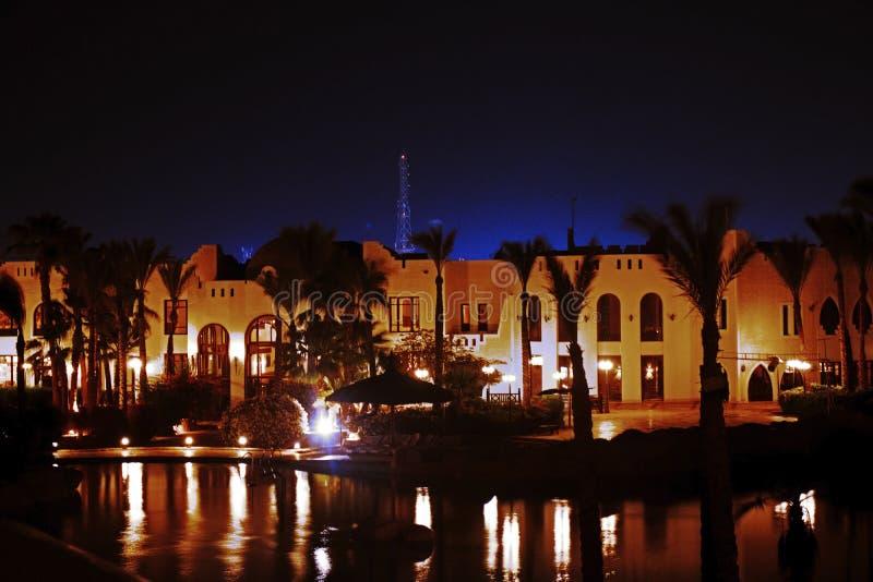 Opinião da noite em construções egípcias com palmas e piscina fotos de stock