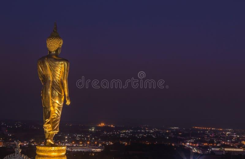 Opinião da noite da estátua dourada grande pública grande de buddha que está em Wat Phra That Kao Noi na província de Nan Tailând imagens de stock royalty free