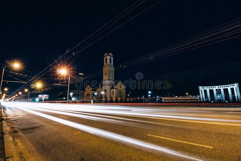 Opinião da noite da igreja através da estrada de cidade com tráfego imagem de stock royalty free