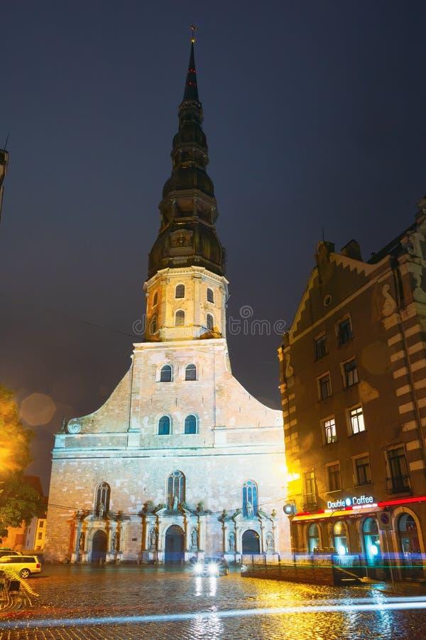 Opinião da noite da igreja do ` s de St Peter na cidade velha Riga Letónia imagens de stock