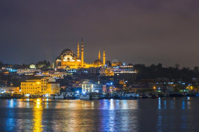 Opinião da noite da mesquita Rustem Pasha Mosque de Suleymaniye da arquitetura da cidade de Istambul com os barcos de turista de  imagem de stock