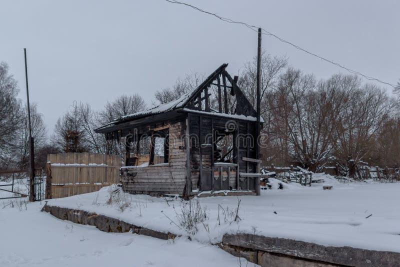 Opinião da noite na casa de madeira pequena queimada na floresta do inverno fotos de stock
