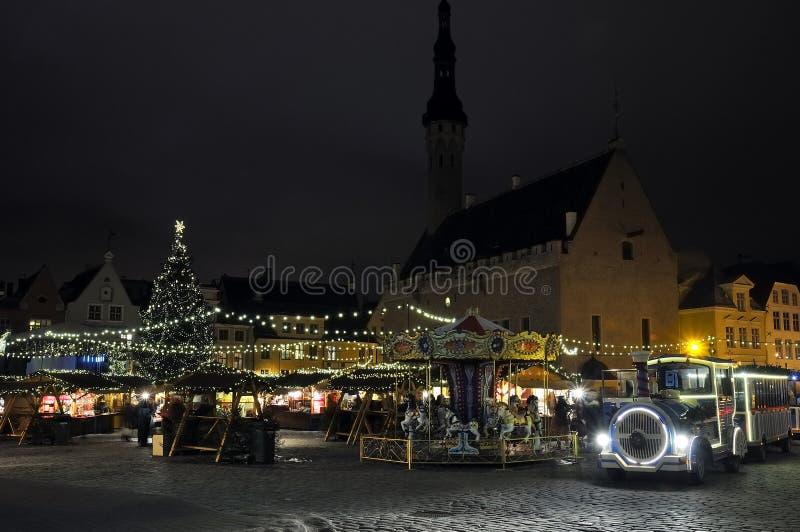 Opinião da noite na locomotiva do carrossel e de vapor do Natal em Tallinn, Estónia foto de stock