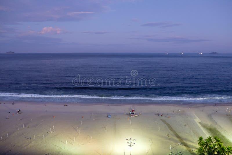 A opinião da noite da praia de Copacabana durante o por do sol no início da noite, tomada do telhado de um hotel, céu é roxa Rio  imagens de stock royalty free