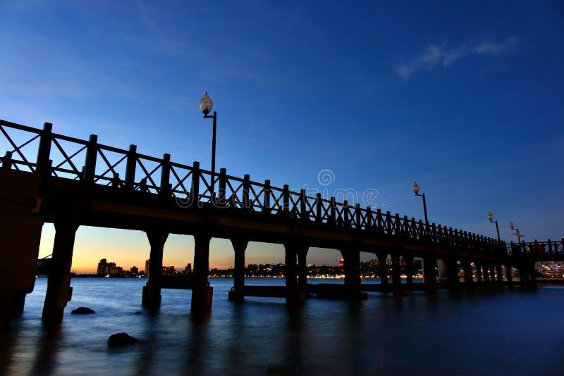 Opinião da noite da silhueta de madeira da passagem com arquitetura da cidade no riverbank fotografia de stock royalty free