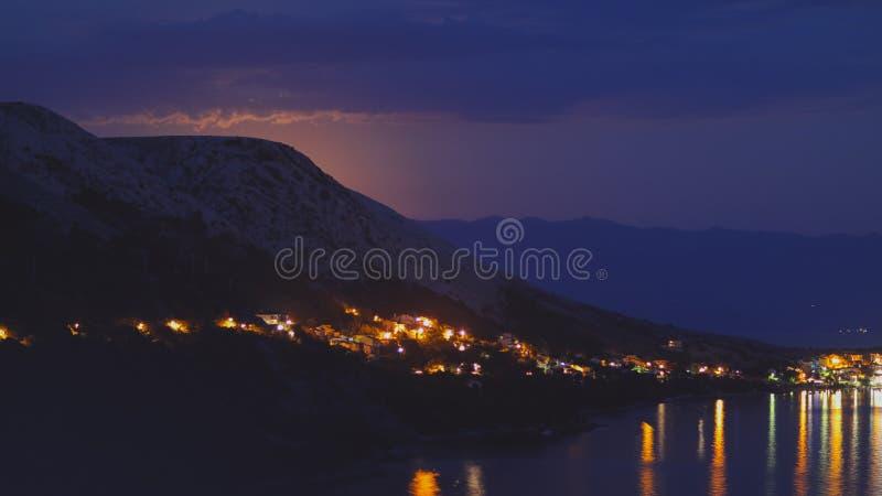 Opinião da noite sob a luz de lua na cidade em uma costa do mar de adriático do monte rochoso na Croácia, tons diferentes da cor fotografia de stock
