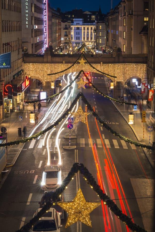 Opinião da noite sobre Kungsgatan, uma rua central de Éstocolmo, decorada com luzes de Natal durante a época natalícia foto de stock