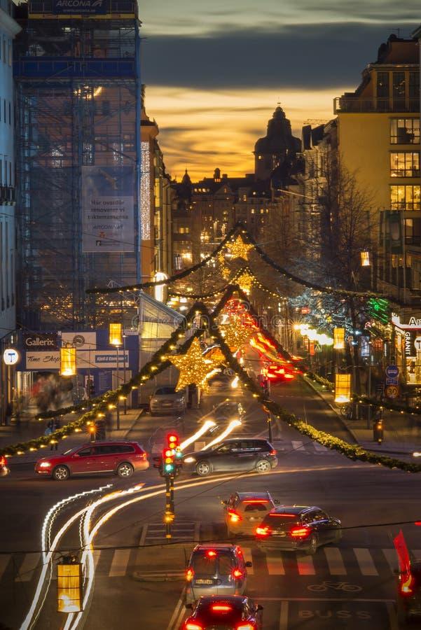 Opinião da noite sobre Kungsgatan, uma rua central de Éstocolmo, decorada com luzes de Natal durante a época natalícia, por do so fotos de stock royalty free