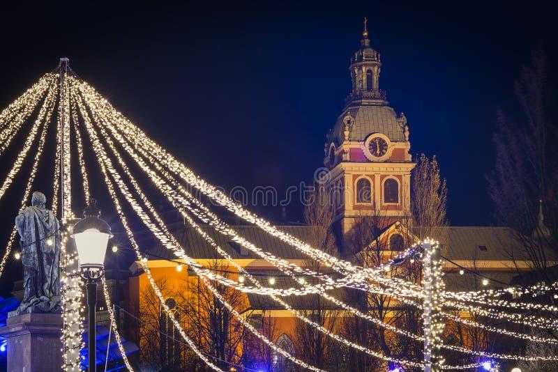 A opinião da noite sobre Kungstradgarden e a igreja de Jacob de Saint decorada com luzes conduzidas durante o Natal temperam fotos de stock