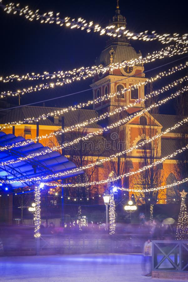 A opinião da noite sobre a pista de patinagem de Kungstradgarden e a igreja de Jacob de Saint decorada com luzes conduzidas duran fotos de stock