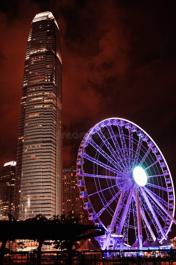 Opinião da noite da terraplenagem à roda de Ferris com um prédio Hon Kong fotos de stock