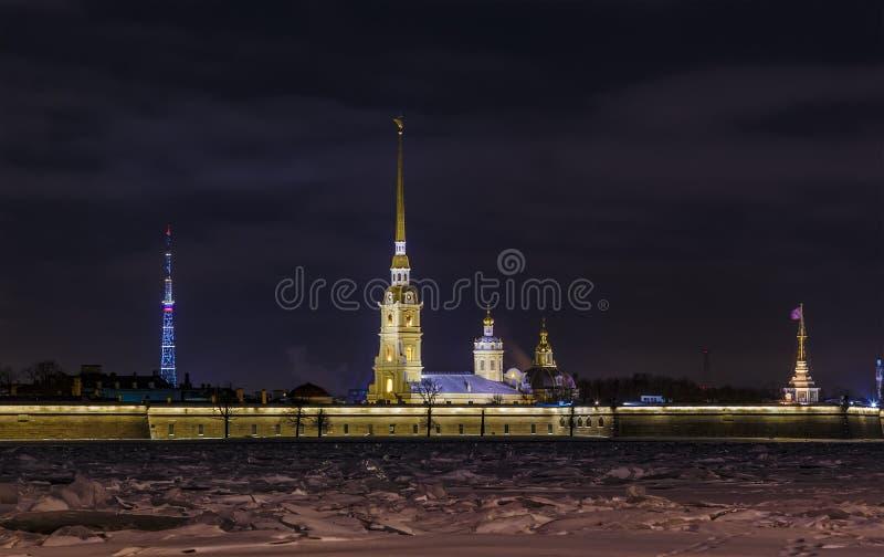 Opinião da noite da terraplenagem de Neva River ao Peter e ao Paul Fortress situados na ilha de Zayachy A torre de sino do Peter imagem de stock