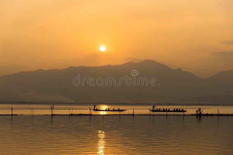 Opinião da paisagem - barco de pá do barqueiro no lago da lagoa Phayao de Kwan no tempo do evenign no phayao Tailândia imagem de stock royalty free