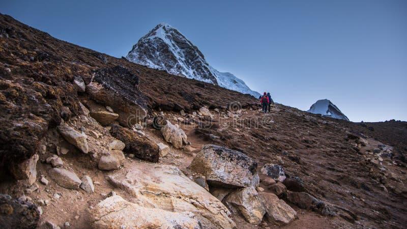 Opinião da paisagem o trajeto e os dois montanhistas que andam à parte superior de Kala Patthar imagem de stock