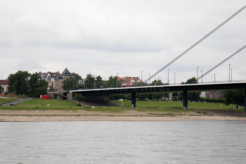 Opinião da parte na ponte e em sua construção e o exterior de construção sob o céu nebuloso no riverbank de rhine no sseldorf do  fotos de stock royalty free