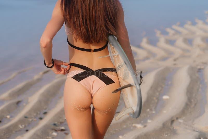 Opinião da parte traseira das nádegas 'sexy' fêmeas no biquini e na prancha em sua mão na praia imagens de stock