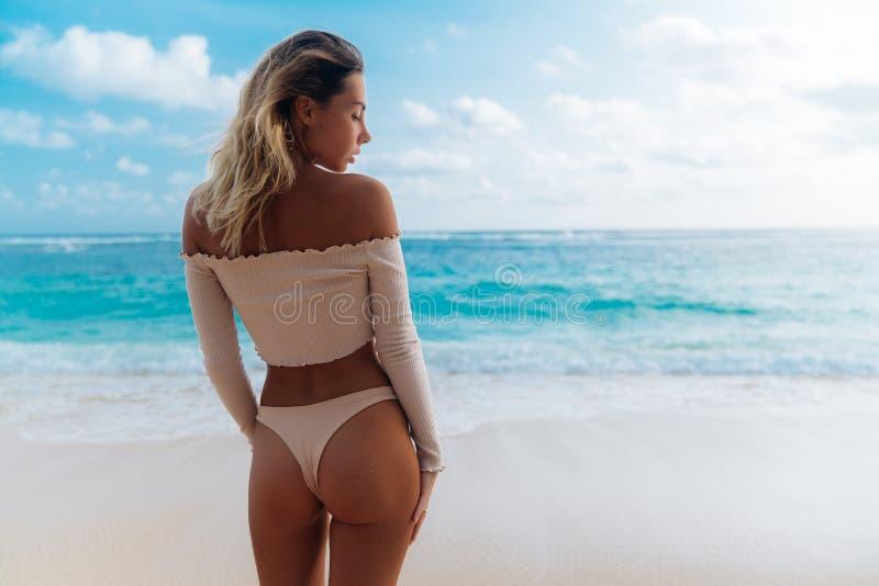 Opinião da parte traseira a menina com montante no biquini bege da cor que descansa na praia abandonada fotos de stock