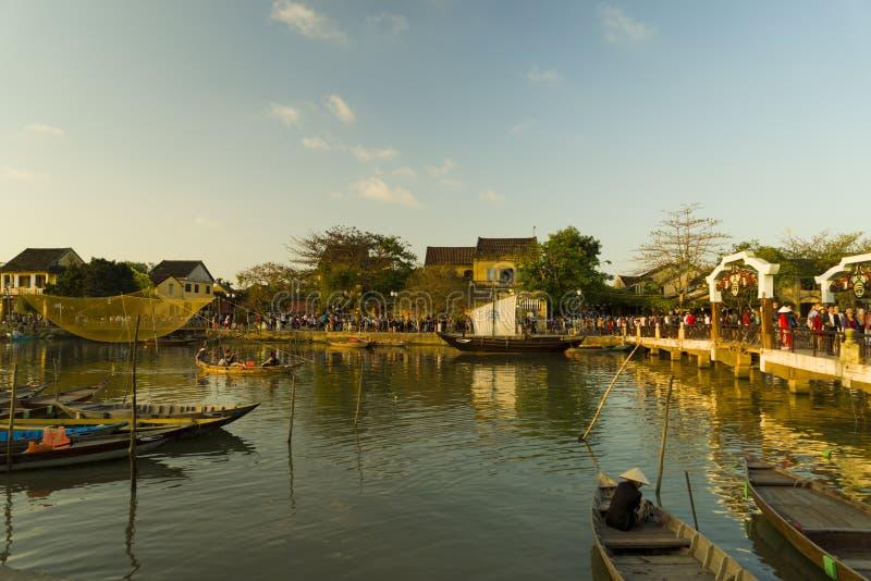 Opinião da rua com barcos tradicionais em um fundo da cidade antiga em Hoi An Vietnam imagens de stock royalty free