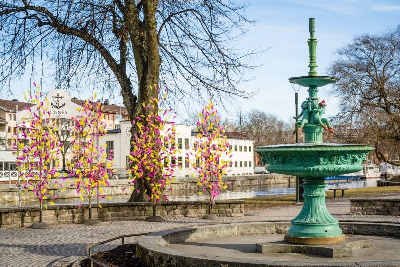 Opinião da rua da fonte inativa com as penas coloridas tradicionais em árvores para decorações da Páscoa em Upsália, Suécia, Euro foto de stock royalty free