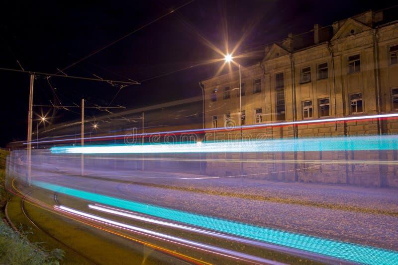 Opinião da rua da noite com os projétis luminosos do bonde na cidade de Daugavpils foto de stock royalty free