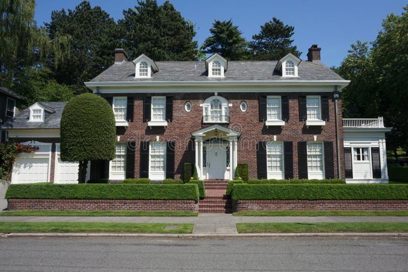 Opinião da rua de uma casa colonial do tijolo em uma vizinhança afluente foto de stock