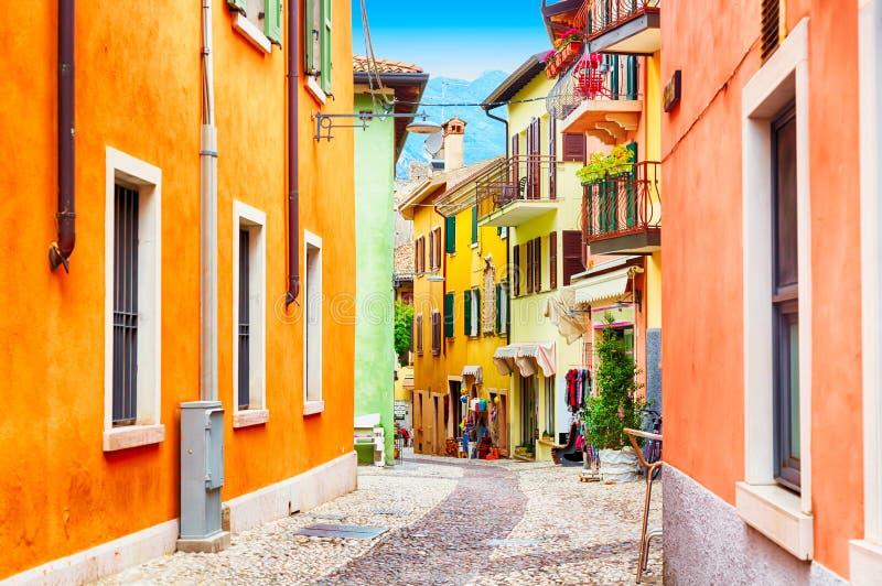 Opinião da rua do estreito da cidade pequena com as casas coloridas em Malcesine, Itália durante o dia ensolarado Lago bonito Gar imagem de stock royalty free