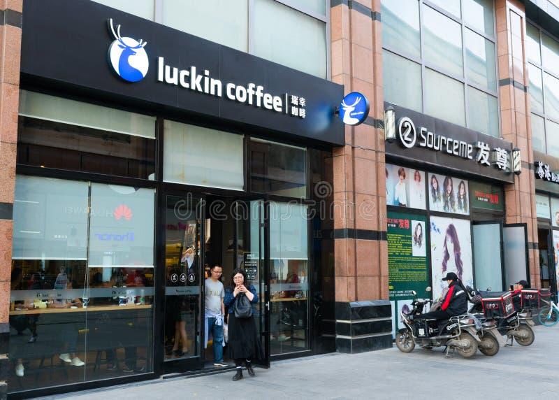 Opinião da rua o povo chinês que sae de uma cafetaria de Luckin em Wuhan China imagens de stock