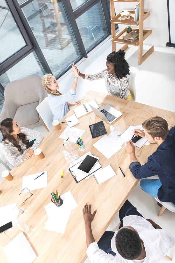 opinião de ângulo alto as mulheres de negócios multiculturais que dão a elevação cinco durante o seminário fotos de stock royalty free