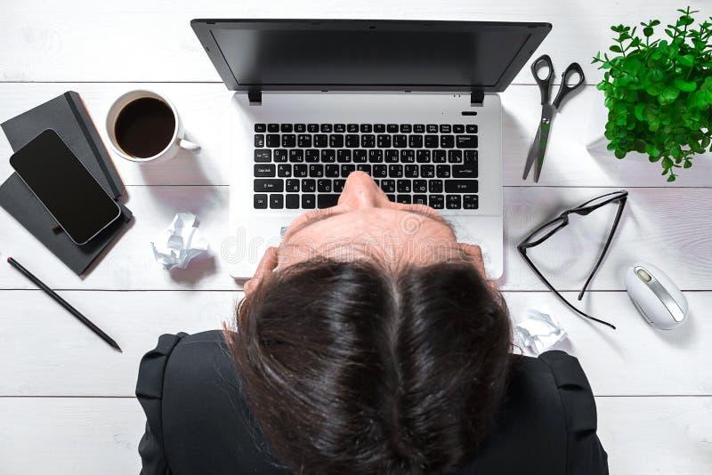 Opinião de ângulo alto de uma morena nova que trabalha em sua mesa de escritório com originais e portátil imagem de stock royalty free