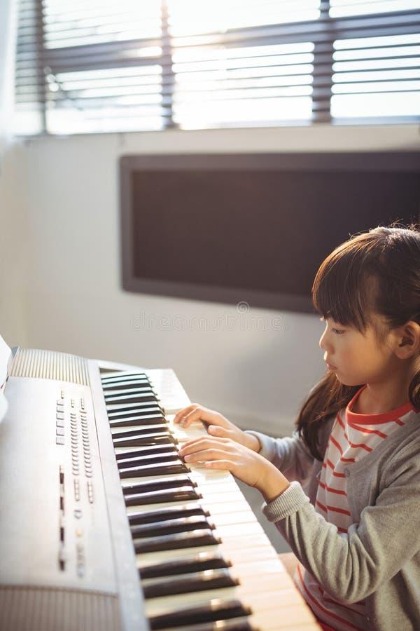 Opinião de ângulo alto do piano praticando concentrado da menina na classe fotos de stock