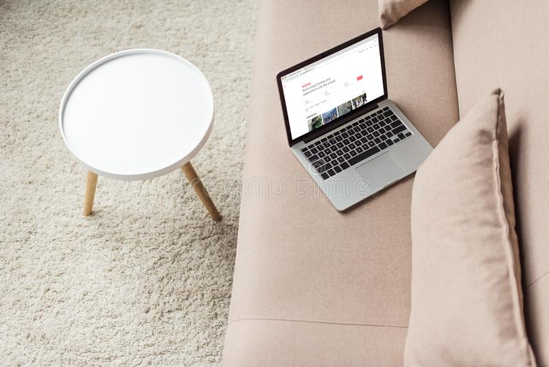 opinião de ângulo alto do portátil que está no sofá acolhedor com Web site do airbnb imagem de stock royalty free