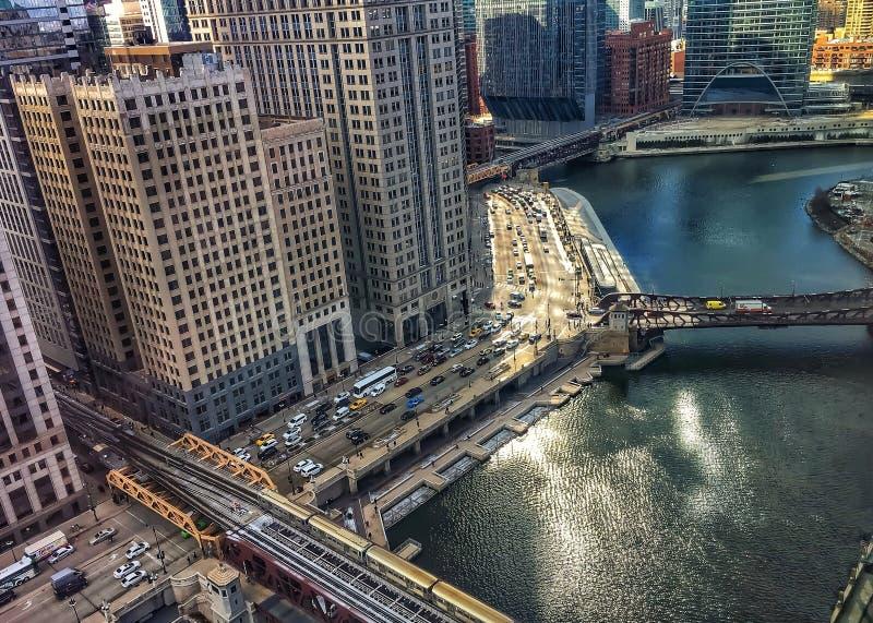 Opinião de ângulo alto do trem do EL que passa sobre águas de brilho da manhã de Chicago River em março no inverno foto de stock royalty free