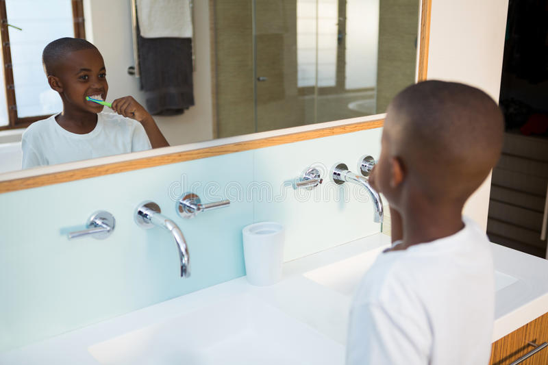Opinião de ângulo alto dos dentes de escovadela do menino vistos da reflexão de espelho imagem de stock