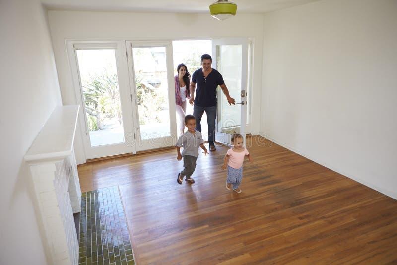 Opinião de ângulo alto a família que explora a casa nova em dia movente fotografia de stock royalty free