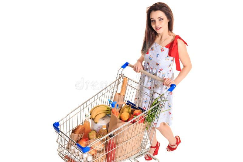 Opinião de ângulo alto a menina que sorri na câmera ao empurrar um carrinho de compras completamente com os mantimentos isolados  imagens de stock royalty free