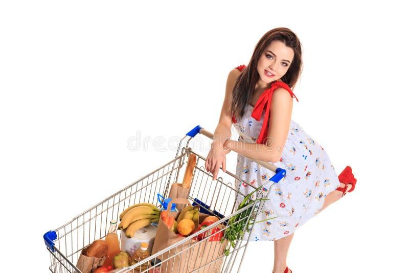 Opinião de ângulo alto a menina que sorri na câmera ao empurrar um carrinho de compras completamente com os mantimentos isolados  imagem de stock