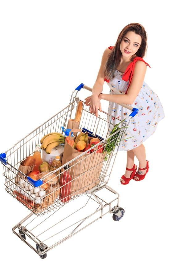 Opinião de ângulo alto a menina que sorri na câmera ao empurrar um carrinho de compras completamente com os mantimentos isolados  foto de stock royalty free