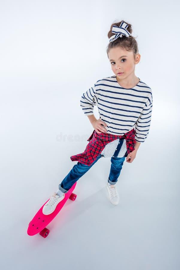 Opinião de ângulo alto a menina séria que está com skate fotos de stock