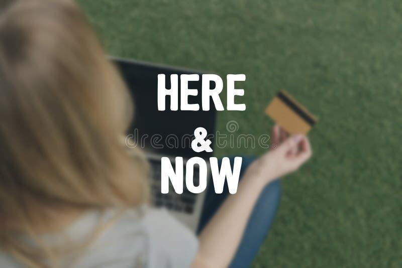 opinião de ângulo alto a mulher que faz a e-compra com portátil ao sentar-se na grama, aqui e agora inscrição imagens de stock royalty free