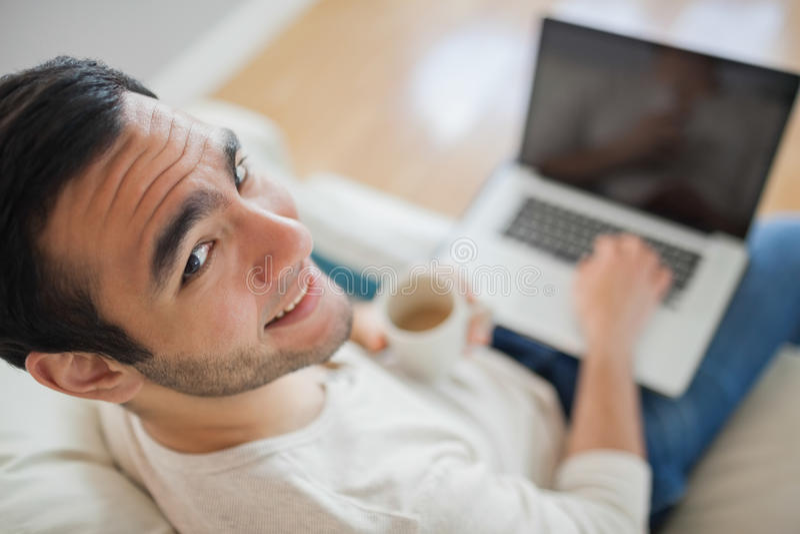Opinião de ângulo alto o homem novo de sorriso que usa seu portátil foto de stock royalty free