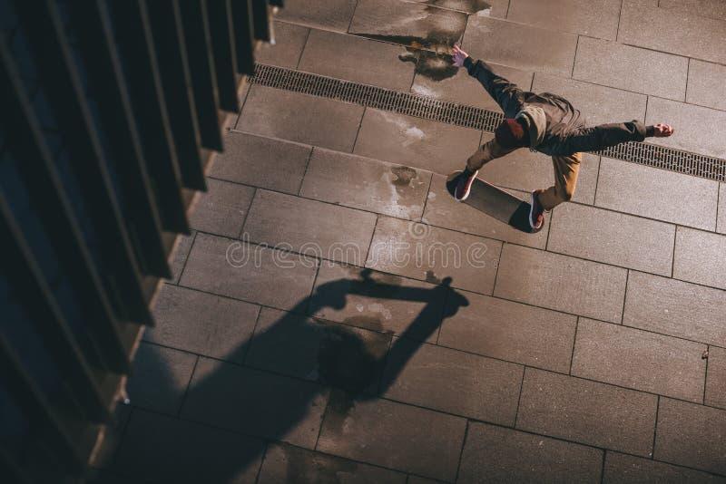 opinião de ângulo alto o skater na execução moderna do streetwear fotografia de stock