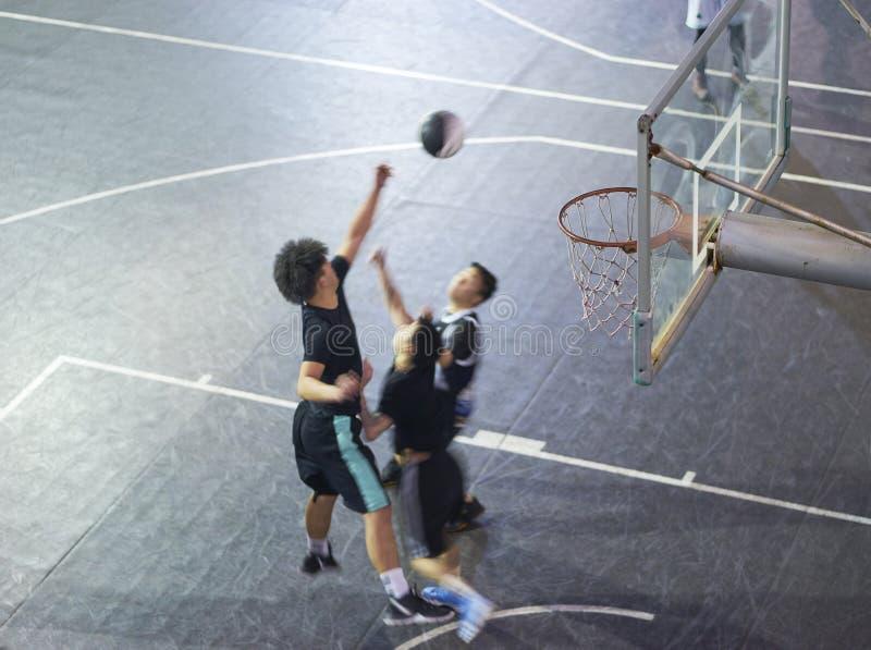 Opinião de ângulo alto os povos asiáticos novos que jogam o basquetebol exterior na noite imagens de stock