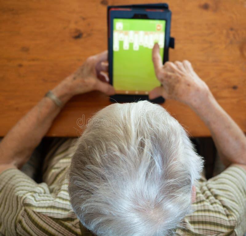 Opinião de ângulo alto uma mulher idosa que joga o solitário em uma tabela fotografia de stock royalty free