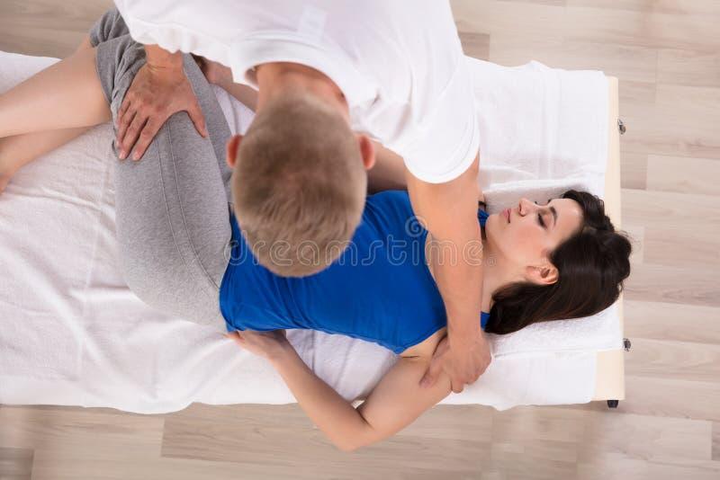 Opinião de ângulo alto uma mulher que recebe a massagem pelo terapeuta imagens de stock