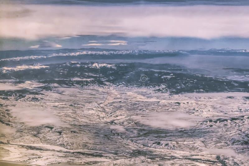 Opinião de Arial do terreno coberto de neve com as montanhas na distância e algumas baixas nuvens sobre um rio e uma cidade e um  imagem de stock royalty free